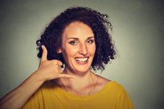 做电话我的可爱的少妇标志和微笑 免版税库存图片