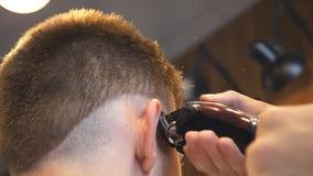 做男性理发的美发师的胳膊对有飞剪机的顾客在沙龙 剪头发的他的发式专家的手 影视素材