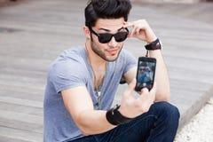 做男性纵向自smartphone年轻人 免版税库存照片