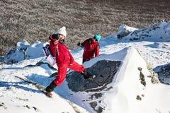 做疯狂的姿势在多雪的岩石,冬天t的母亲和孩子 免版税库存图片