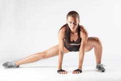 做白种人赞成的女运动员舒展在白色bac的锻炼 免版税库存照片