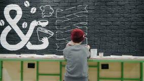 做白色设计的创造性的画家背面图年轻女性画家在咖啡店的黑砖墙 股票视频