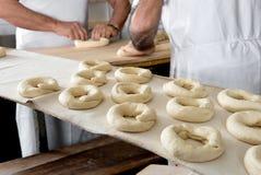 做百吉卷的面包师面团 免版税库存照片