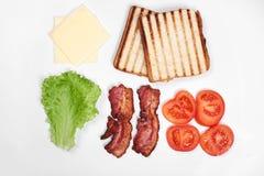 做的三明治成份 新鲜蔬菜,蕃茄,面包, becon,乳酪 隔绝在白色背景,上面 库存图片