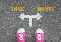 做的决定在交叉路-爱或金钱 免版税图库摄影