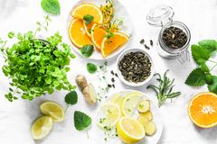 做的冷的芳香绿茶成份-烘干绿茶,柠檬,桔子,姜,薄菏,在轻的背景的迷迭香,顶面v 库存图片