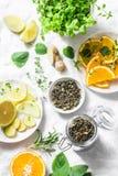 做的冷的芳香绿茶成份-烘干绿茶,柠檬,桔子,姜,薄菏,在轻的背景的迷迭香,顶面v 库存照片
