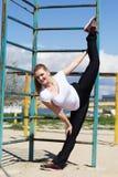 做的女孩舒展锻炼在标志横线附近 免版税库存照片