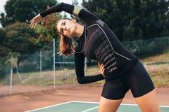做的女运动员舒展在网球场的锻炼 免版税图库摄影