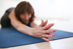 做的妇女舒展在瑜伽席子的锻炼 免版税库存照片