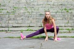 做的妇女舒展锻炼在公园 免版税库存照片
