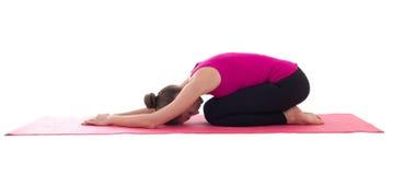 做的少妇舒展在wh隔绝的瑜伽席子的锻炼 免版税库存照片