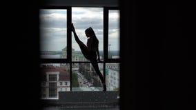 做的年轻女人舒展站立在慢动作的体育健身房锻炼的腿 股票录像