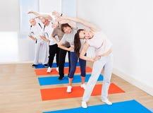 做的教练员和的顾客舒展锻炼 免版税库存照片