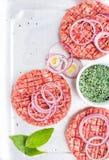 做的汉堡三道未加工的绞细牛肉肉炸肉排与洋葱圈和香料在白色木背景,顶视图 免版税库存照片