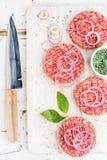做的汉堡未加工的绞细牛肉肉炸肉排与洋葱圈、香料和刀子在白色木板 图库摄影