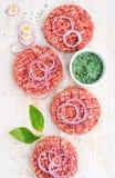 做的汉堡未加工的绞细牛肉肉炸肉排与洋葱圈和香料在白色木背景 免版税库存照片