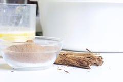 做的酥皮点心卷成份 被击碎的桂香和糖在一个玻璃容器被混合 附近的谎言肉桂条 库存照片