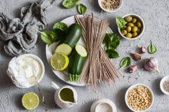 做的绿色soba碗-夏南瓜,菠菜, soba,在灰色背景,顶视图的酸奶成份 健康素食食物骗局 库存照片