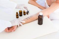 做皮肤刺测试的医生在她的患者 免版税库存图片