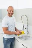 做盘的微笑的年轻人在厨房水槽 免版税库存照片