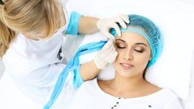 做眼眉纹身花刺的专业美容师在妇女面孔 在美容院,特写镜头的永久眉头构成 Cosmetolog 图库摄影