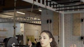 做着与杠铃的蹲坐在现代健身房年轻女运动员的画象  股票录像