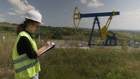 做研究在油泵单位附近注意信息数据对她的剪贴板的年轻女性工程师- 股票视频