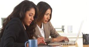 做研究的不同种族的女实业家在书桌 免版税图库摄影