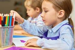 做礼品券的孩子在幼儿园 免版税库存照片