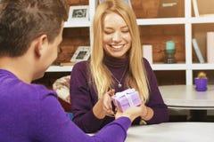 做礼物的年轻人对女孩 免版税图库摄影