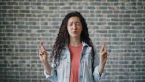 做祈祷的手势的害怕的女孩画象在砖墙背景 股票录像