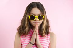 做祷告的十几岁的女孩,思考 桃红色背景 免版税图库摄影