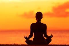 做禅宗在海滩的健康妇女瑜伽凝思 免版税库存照片