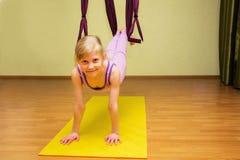 做空中瑜伽的小女孩行使,室内 免版税库存照片