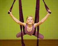 做空中瑜伽的小女孩行使,室内 免版税图库摄影