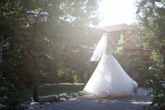 做竖趾旋转的新娘在公园 免版税库存照片