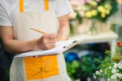 做笔记的亚裔男性卖花人的播种的图象在花店 库存照片