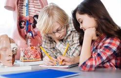 做笔记的体贴的年轻学生 免版税图库摄影