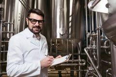 做笔记的勤勉人在啤酒工厂 库存照片
