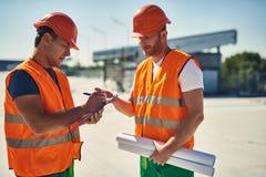 做笔记的友好建造者谈话和他的同事 库存照片