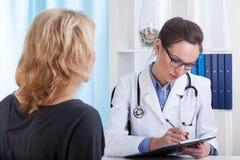 做笔记的女性医生 免版税库存照片