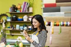 做笔记的微笑的亚裔女性卖花人在花店柜台 库存图片