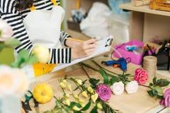 做笔记的微笑的亚裔女性卖花人在花店柜台 免版税图库摄影