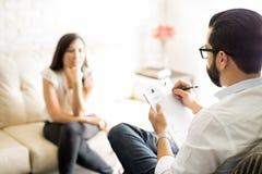 做笔记的心理学家在与妇女患者的一个会议期间 库存照片