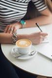 做笔记的手的特写镜头图片在纸、站立在咖啡馆的一张桌上的杯子cappucciono和膝上型计算机 库存照片