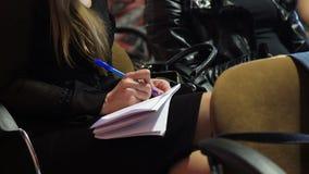 做笔记的播种的观点的业务会议的女性参加者在纸 股票录像