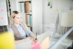 做笔记的沉思夫人,当观看介绍在办公室时 免版税图库摄影