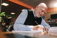做笔记的老人在教室 免版税库存照片
