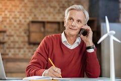 做笔记的老人,当谈话在电话时 图库摄影